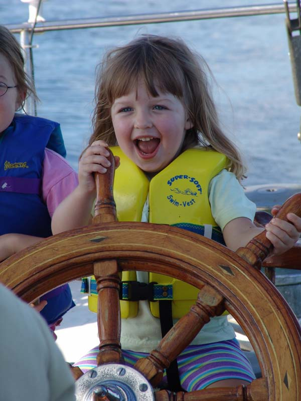 young girl at the helm of viva with big grin